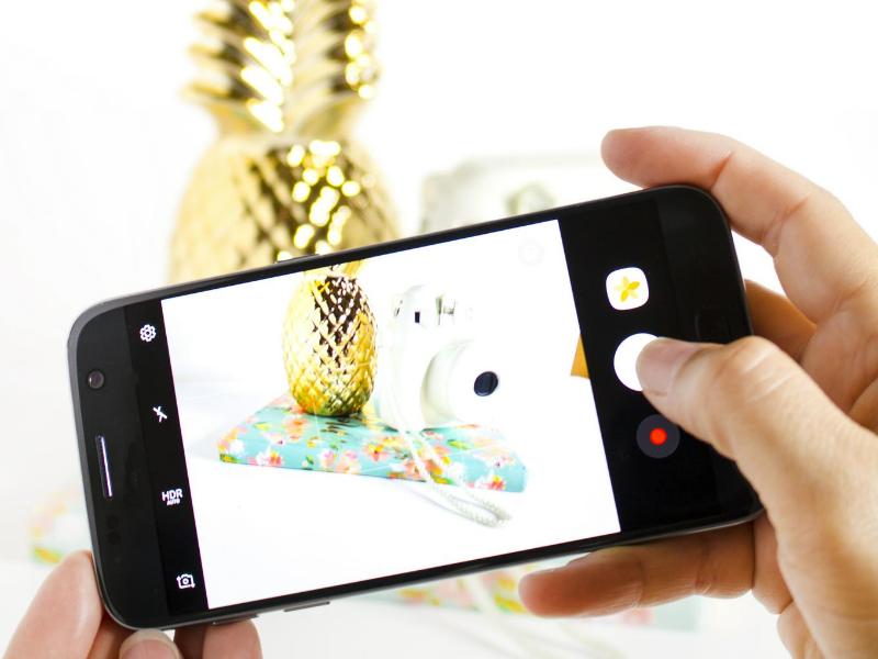 Warum Ihr Logo unbedingt auf Ihre Pins sollte - Ananas mit Handy fotografiert